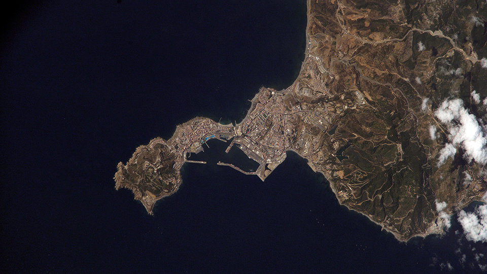 ISS015-E-18808 (21 July 2007) --- Ceuta on the northern African coastline is featured in this image photographed by an Expedition 15 crewmember on the International Space Station. The small Spanish enclave of Ceuta occupies a narrow isthmus of land on the African side of the Strait of Gibraltar. This view illustrates the sharp contrast in land cover between urban Ceuta (pink to white residential and industrial rooftops at center), the bay formed by seawalls to the north of the city, and the higher elevations of Monte Hacho forming the end of the isthmus. Green, vegetated slopes surround the Spanish fort atop the mountain, which commands a clear view of the Strait of Gibraltar to the northwest (not shown).  Several small dots are visible near the coastline to the northwest and south of Ceuta -- these are small pleasure or fishing boats.