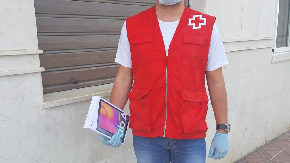 Un voluntario de Cruz Roja, con una de las tabletas repartidas por el instituto.